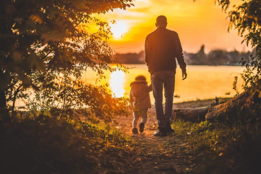 Photo of a father and son hiking by a lake.